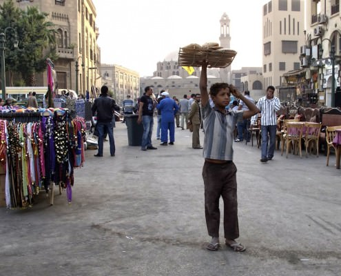 A boy selling bread in the square in front of the Mosque of Sayyidna al-Hussein