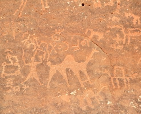 Images of people and camels carved into a rock wall at Wadi Rum