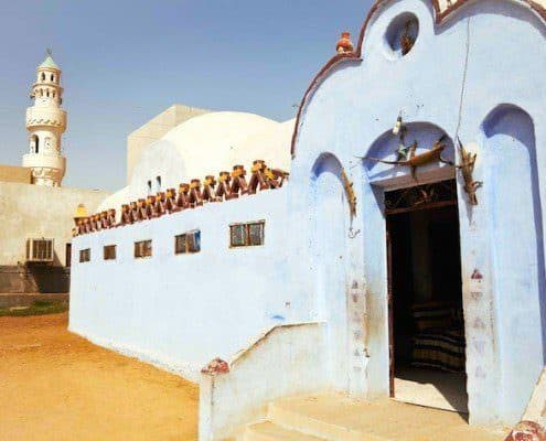Nubian village, blue and white houses with a mosque in the background, Egypt.