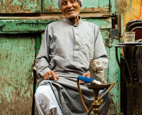 Old Egyptian man sits at a street cafe smoking sheesha in Islamic Cairo