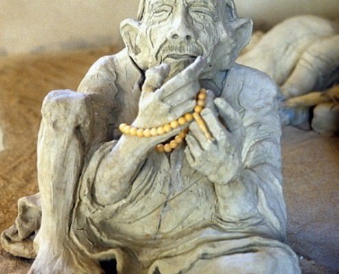Clay sculpture of an old man sitting