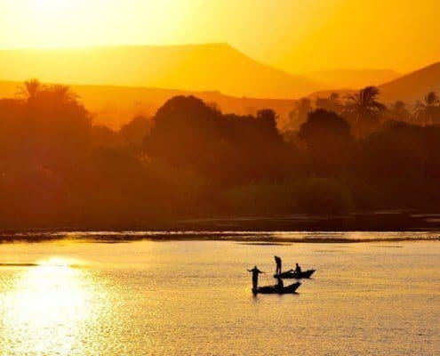 Silhouettes of fishermen on traditional boats at sunset