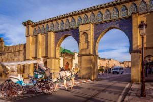 A tourist coach crosses Bab Moulay Ismail in front of the famous mausolem on December 23 2014 in Meknes, Morocco