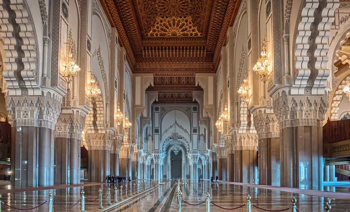 Places to Visit in Casablanca - Hassan II Mosque interior corridor with columns in Casablanca Morocco. Arabic arches, ornaments, chandelier and lighting