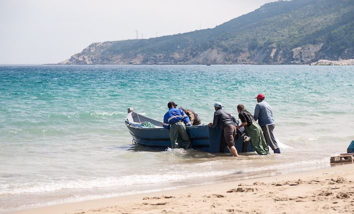 Tangier Morocco Attractions - Unidentified men pull a fishing boat to the beach.