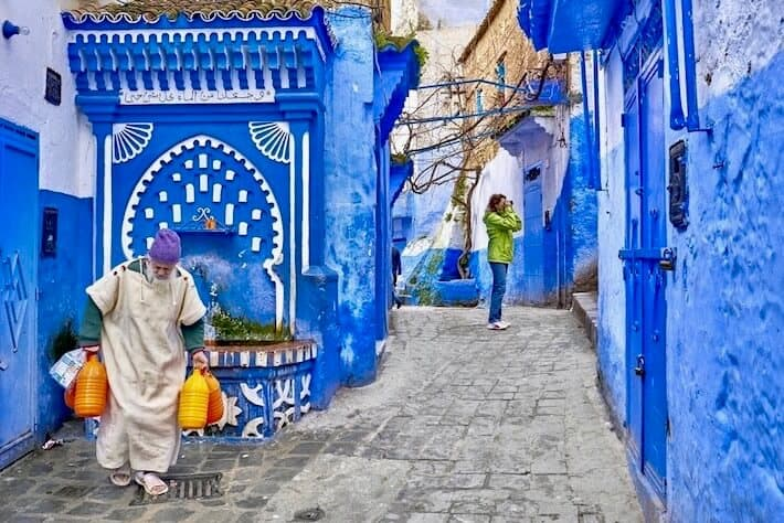 Group tours in Morocco. Local man carries water from the well. Chefchaouen, Morocco