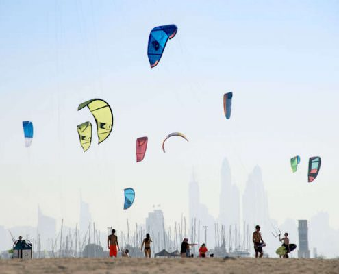 Kite beach in Jumeirah, Dubai, United Arab Emirates. A stretch of the beach designated for the kite surfers. The beach-goers are a colorful mix of different nationalities.