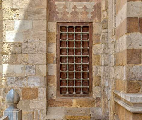 Window with iron bars on exterior stone bricks wall of Amir Aqsunqur Mosque (Blue Mosque)