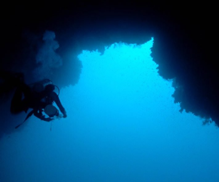 Technical diver passing under the Arch of the Blue Hole in Dahab