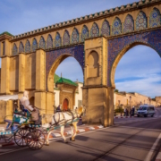 Private Guided Tours of Morocco - Tourist coach crosses Bab Moulay Ismail in front of the famous mausoleum in Meknes, Morocco